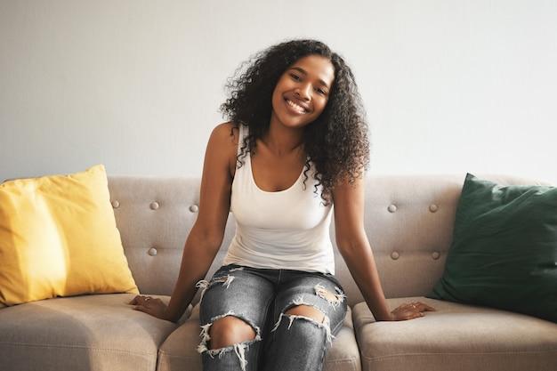 Konzept für menschen, lebensstil, freizeit, ruhe und entspannung. entzückende schöne junge dunkelhäutige frau, die weißes trägershirt und zerrissene jeans mit glücklichem sorglosem blick trägt, während sie zu hause auf der couch entspannt