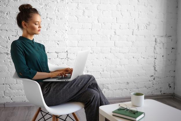 Konzept für menschen, lebensstil, freizeit, technologie und kommunikation. modische junge bloggerin, die aus der ferne mit wlan auf einem tragbaren computer auf ihrem schoß arbeitet, schnell tippt und morgenkaffee trinkt