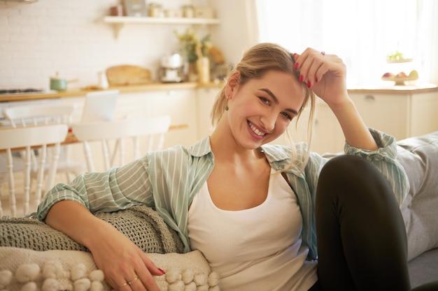Konzept für menschen, lebensstil, häuslichkeit, freizeit und entspannung. charmante junge blonde frau mit pferdeschwanz, die sich drinnen auf dem sofa entspannt und sorglos aussieht, lacht und die hand auf ihrer stirn hält