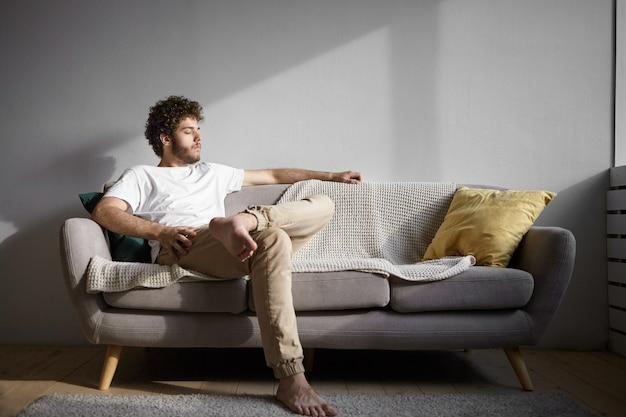 Konzept für menschen, lebensstil, ruhe und entspannung. bild des gutaussehenden kerls mit nackten füßen, die drinnen ruhen, auf gemütlicher couch sitzen und augen schließen. stilvoller junger mann mit stoppeln, die allein zu hause entspannen