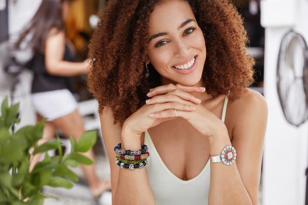 Konzept für menschen, schönheit, ethnische zugehörigkeit und mimik. attraktives afroamerikanisches weibliches modell ruht im café mit freund oder liebhaber