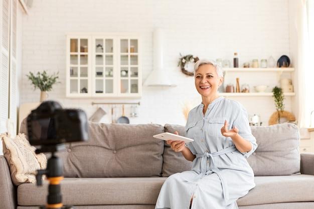 Konzept für menschen, technologie und moderne elektronische geräte. bild des schönen kurzhaarigen älteren weiblichen bloggers, der auf couch im kücheninnenraum unter verwendung des digitalen tabletts sitzt