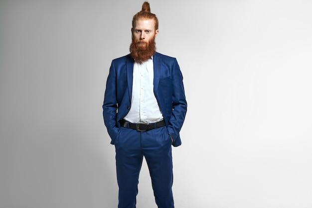 Konzept für menschen, unternehmen, beruf, stil, mode und herrenbekleidung. gut aussehender junger kaukasischer bärtiger männlicher büroangestellter, der eleganten blauen anzug und haarknoten trägt und im studio mit den händen in den taschen aufwirft