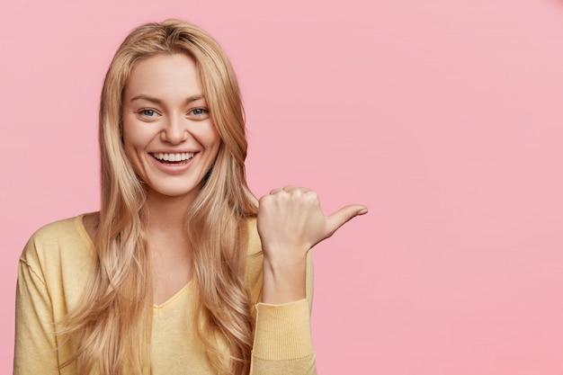 Konzept für menschen, werbung und positivität. glückliche junge frau mit angenehmem aussehen und lächeln, zeigt mit dem daumen zur seite an leerem rosa kopienraum für ihren werbetext oder hörer an.