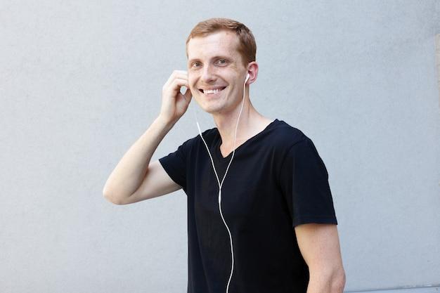 Konzept für mode, emotionen und menschen - nahaufnahme des porträts eines schönen männlichen mannes mit rothaariger. sommersprossen auf dem smartphone mit kopfhörern, tänze, gesten fröhlich, inspiriert von lieblingsmusik
