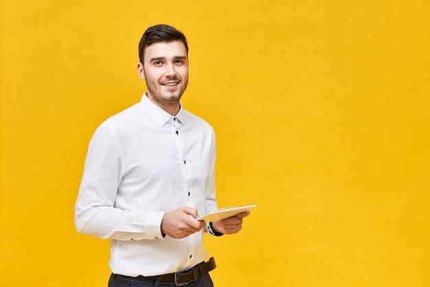 Konzept für moderne technologie und elektronische geräte. stilvoller positiver junger männlicher manager, der digitales tablett für arbeit verwendet. geschäftsmann in der formellen kleidung, die tragbaren computer des touchpads hält