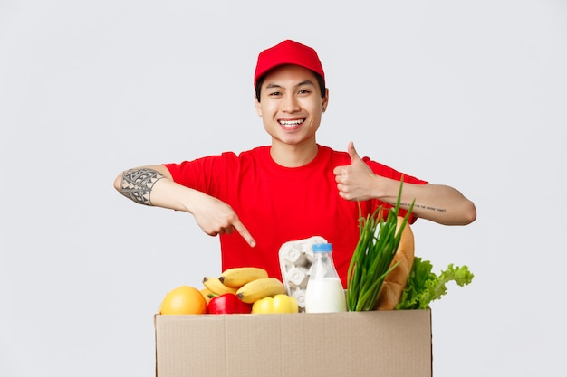 Konzept für online-shopping, lebensmittellieferung und internet-shops. lächelnder freundlicher kurier in rotem t-shirt und mütze, daumen hoch zeigen, lebensmittelpaket bestellen, produkte zeigen, spediteurservice empfehlen.