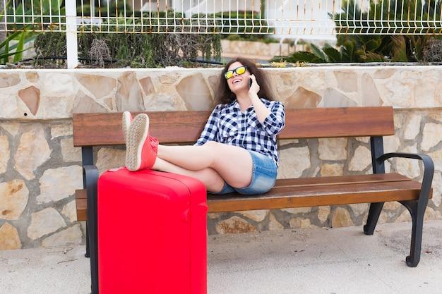 Konzept für reisen, tourismus, technologie und menschen. glückliche junge frau sitzt auf der bank und stellt ihre füße auf den koffer