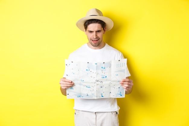 Konzept für reisen, urlaub und tourismus. mann, der während der reise verwirrt auf die karte schaut, kann nicht verstehen, steht auf gelbem hintergrund
