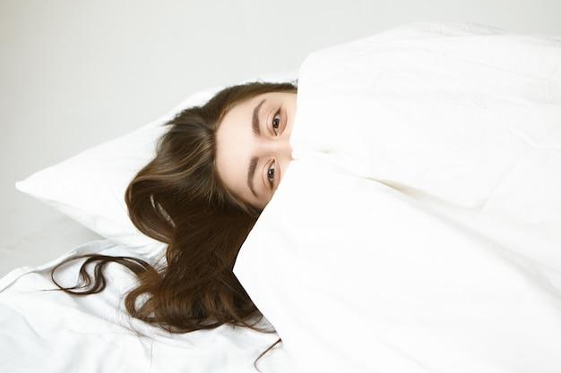 Konzept für schlafenszeit, ruhe und entspannung. verspielte attraktive junge frau mit schönen augen und dunklem haar, das sich auf weißem kissen entspannt, sich hinter decke versteckt und mit glücklichem ausdruck schaut