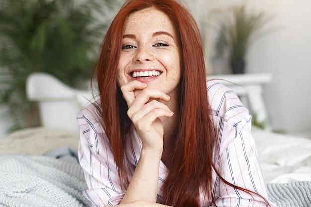 Konzept für schönheit, jugend, freude und glück. entzückende süße junge rothaarige sommersprossige frau in gestreifter nachtwäsche, die fröhlich lächelt und glücklichen moment genießt, während sie freizeit zu hause verbringt