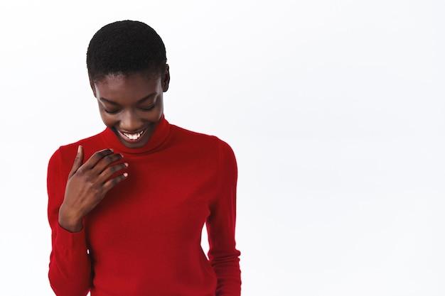 Konzept für schönheit, mode und menschen. taillenporträt einer attraktiven schüchternen und dummen afroamerikanischen frau im roten rollkragenpullover