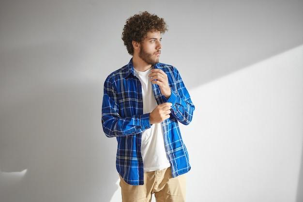 Konzept für stil, mode, kleidung und herrenbekleidung. isolierte ansicht des stilvollen jungen bärtigen männlichen modells mit gewelltem haar, das das tragen des trendigen karierten hemdes aufwirft, wegschaut und manschette zuknöpft