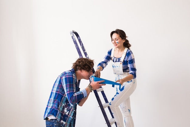 Konzept für teamarbeit, renovierung und reparatur - porträt eines lustigen paares, das die renovierung in der wohnung durchführt.