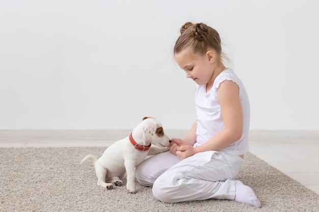 Konzept für tiere, kinder und haustiere - kleines mädchen, das mit süßem welpen auf dem boden sitzt und spielt.