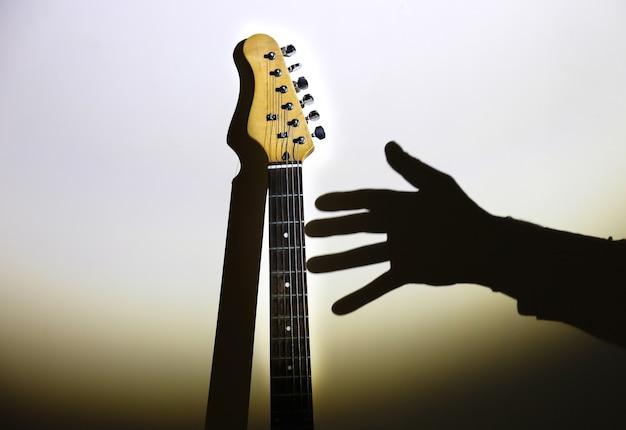 Konzept für unerfüllte träume. e-gitarre auf dem schatten mit der hand des mannes. musiker im rampenlicht. kreatives foto mit hellen schatten.