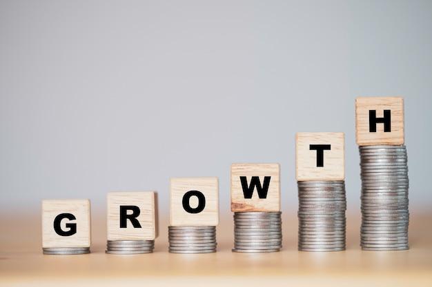 Konzept für unternehmensinvestitionen und gewinnwachstum. wachstumsformulierung auf holzblockwürfel und ablegen auf gestapelten münzen.