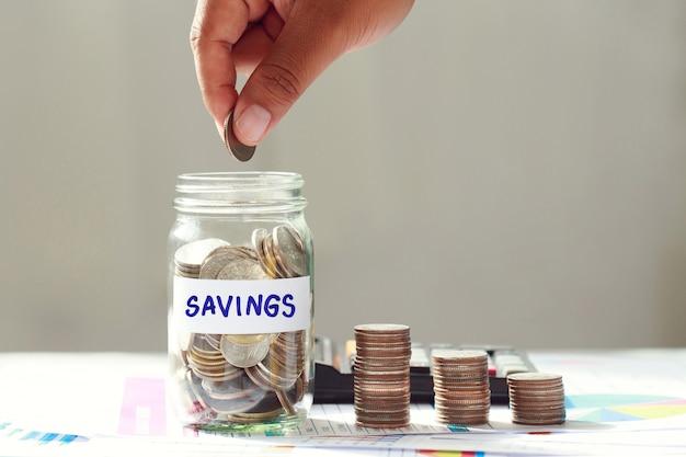 Konzept für wachstum und geld sparen. die hand des mannes legt eine münze in eine glasflasche und einen haufen münzen auf das geschäftsdiagramm auf dem tisch