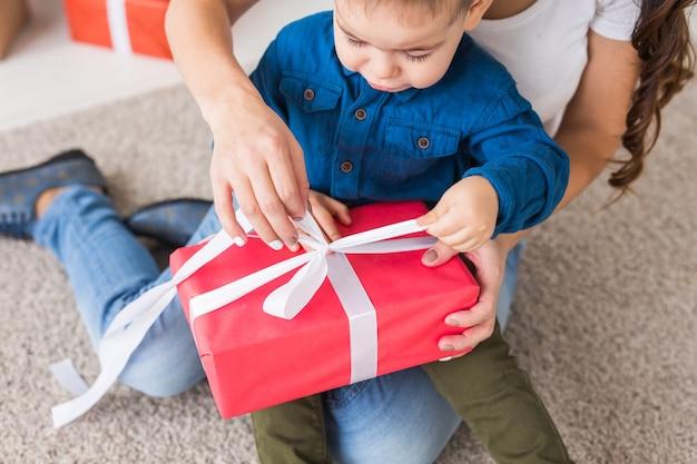 Konzept für weihnachten, alleinerziehende und feiertage - nahaufnahme eines süßen kleinen jungen, der ein weihnachtsgeschenk für seine mutter zu hause hält.