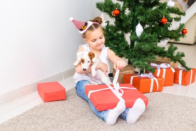 Konzept für weihnachten, haustiere und feiertage - kind in weihnachtsmütze mit einem jack-russell-terrier-welpen.