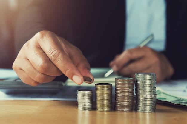 Konzept geld sparen. handholdingmünzen, die stapel auf tabelle im büro setzen