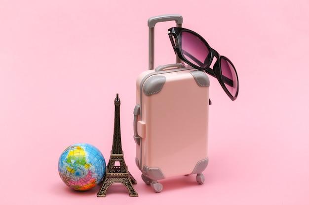 Konzept gereist. mini-reisekoffer aus kunststoff mit sonnenbrille und statuette des eiffelturms, globus auf rosa hintergrund.