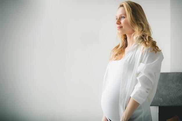Konzept - junges schönes glückliches lächelndes schwangeres kaukasisches blondes mädchen, das im weißen hellen wohnzimmer steht