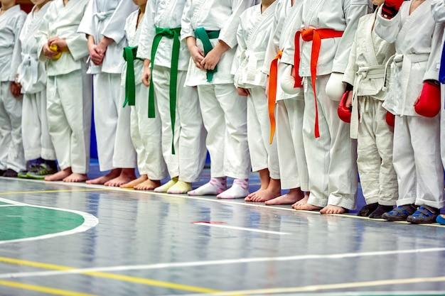 Konzept karate, kampfkunst. bau der studenten in der halle vor dem training. kimono, verschiedene gürtel, verschiedene trainingsstufen