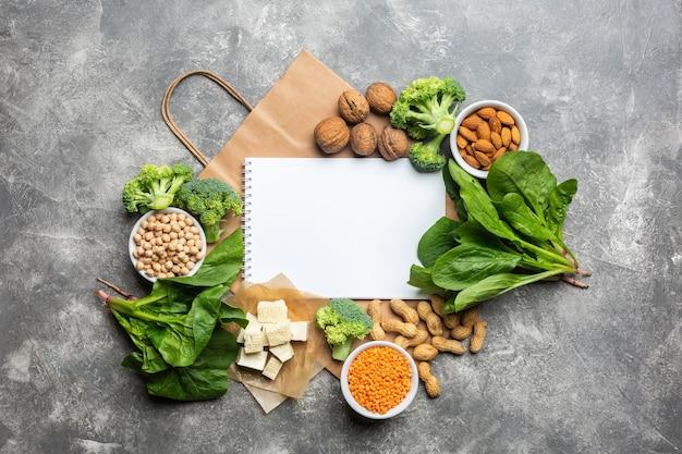 Konzept: kaufen sie gesunde, saubere lebensmittel. proteinquelle für vegetarier: draufsicht von gemüse, nüssen und hülsenfrüchten auf einem konkreten hintergrund mit einer papiertüte und einem weißen notizbuch für eine produktliste.
