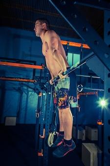 Konzept kraft stärke gesunder lebensstil sport mächtiger attraktiver muskulöser mann im crossfit-fitnessstudio