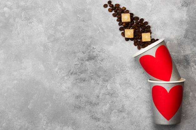 Konzept liebe zum kaffee. graue papierschalen für getränke mit rotem herzen, kaffeebohnen auf einem hellen hintergrund. draufsicht, kopie, raum. essen hintergrund.