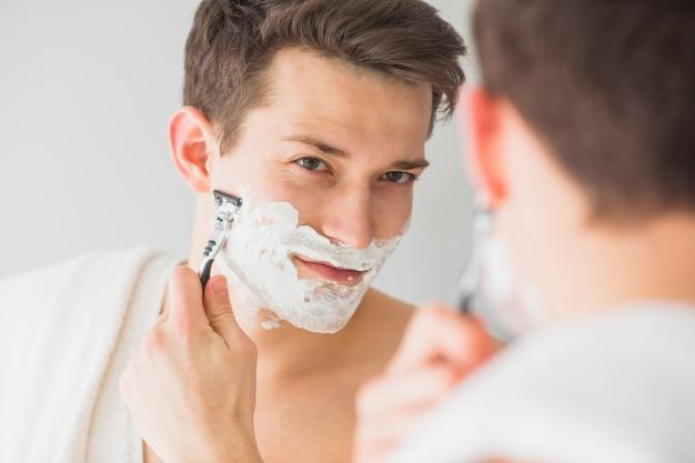Konzept mit attraktivem jungem mann rasieren
