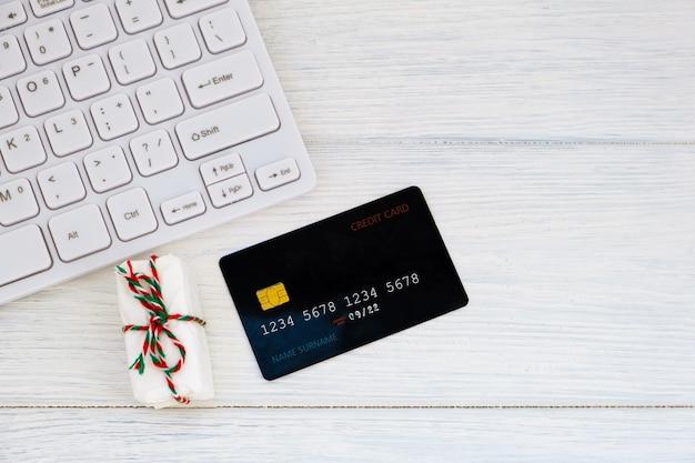 Konzept online-shopping kauf von geschenken. kreditkarte, tastatur und weihnachtsgeschenk auf weißem tisch flach liegen. business-weihnachtsferienkonzept, feiertagsgeschenk-online-einkaufskonzept.