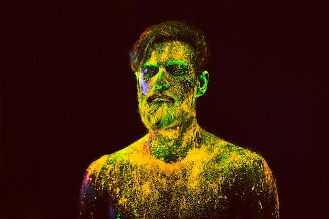 Konzept. porträt eines bärtigen mannes. der mann ist in ultraviolettem pulver gemalt.