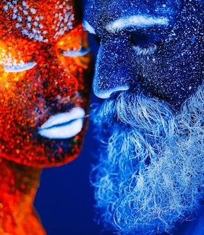 Konzept. porträt eines bärtigen mannes und der frau gemalt im uv-pulver.