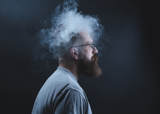 Konzept. rauch umhüllte den schulleiter. porträt eines bärtigen, stilvollen mannes mit rauch. passivrauchen.