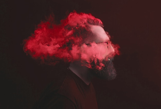 Konzept. rauch umhüllte den schulleiter. porträt eines bärtigen, stilvollen mannes mit rauch.