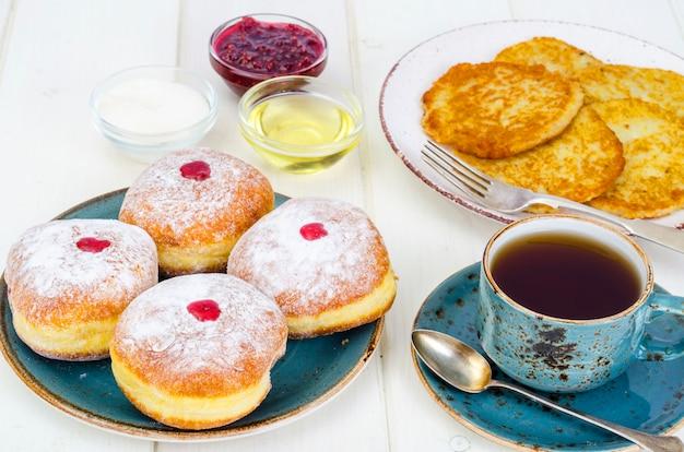 Konzept und hintergrund jüdischer feiertag chanukka. traditionelles essen donuts und kartoffeln pfannkuchen latkes. flachlage oder draufsicht.