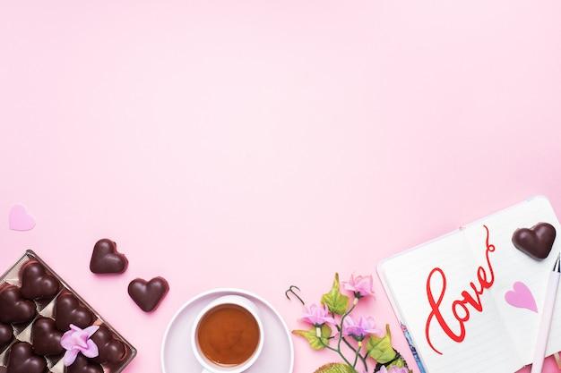 Konzept valentinstag. pralinen und kaffee, herzen auf einem rosa hintergrund. flacher laienkopienraum. grußkarte und geschenk.