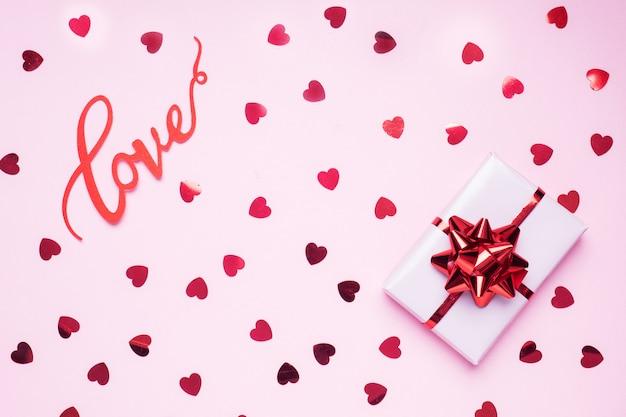 Konzept valentinstag. rosa hintergrund mit roten herzen und geschenk. flacher laienkopienraum. grußkarte und geschenk.