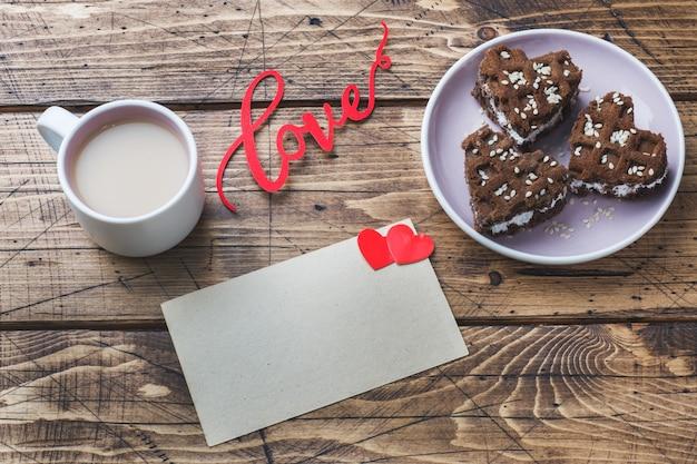 Konzept valentinstag. tasse kaffee und kekse auf einem holztisch. grußkarte. platz kopieren