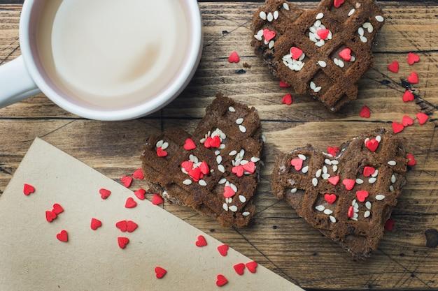 Konzept valentinstag. tasse kaffee und kekse auf einem holztisch. grußkarte.