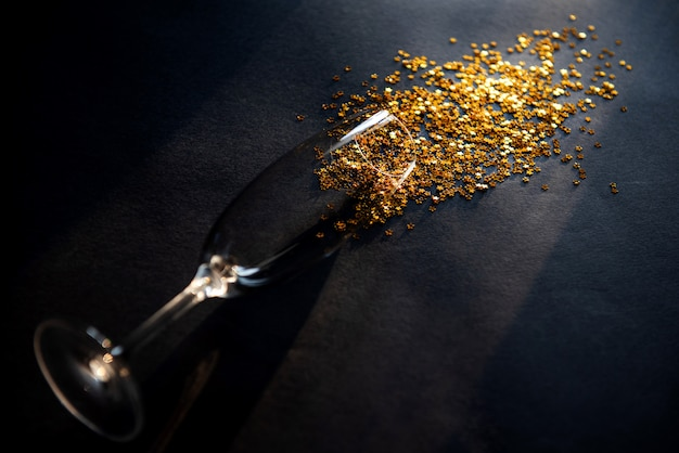 Konzept verschütteter weißwein oder champagner. ende der party. ein glas wein auf einem tisch liegend darin goldene sterne symbolisieren verschütteten wein