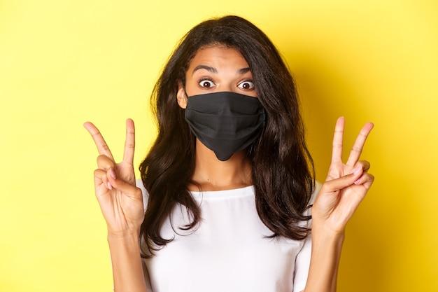 Konzept von coronavirus, pandemie und lebensstil. nahaufnahme eines albernen afrikanisch-ameirkischen mädchens in schwarzer gesichtsmaske, das friedenszeichen zeigt und auf gelbem hintergrund steht