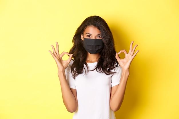 Konzept von coronavirus, pandemie und lebensstil. porträt eines selbstbewussten afroamerikanischen mädchens, das eine schwarze gesichtsmaske trägt, um sich vor covid-19 zu schützen, mit guten zeichen, gelbem hintergrund.