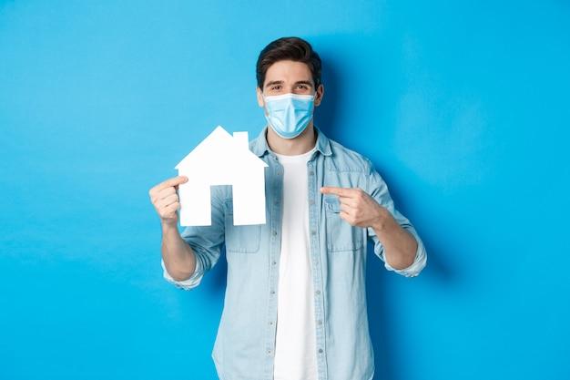 Konzept von coronavirus, quarantäne und sozialer distanzierung. junger mann, der eine wohnung nach miete sucht, geschäftskredite, auf hausmodell zeigt, medizinische maske trägt, blauer hintergrund