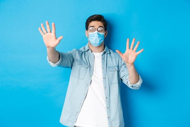 Konzept von coronavirus, sozialer distanzierung und pandemie. mann in medizinischem glas kann in nebligen gläsern nicht sehen, stehend über blauem hintergrund