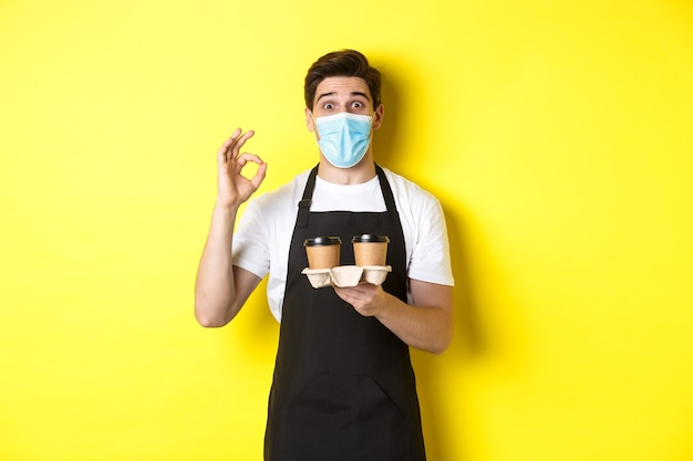 Konzept von covid-19, café und sozialer distanzierung. barista in medizinischer maske und schwarzer schürze garantieren sicherheit, hält kaffeetassen zum mitnehmen und zeigt ok-zeichen, gelber hintergrund