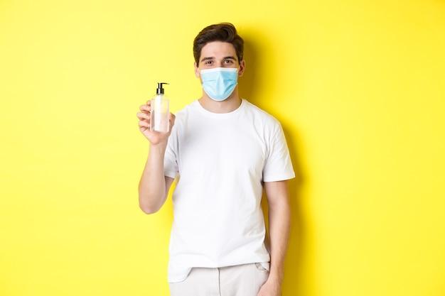 Konzept von covid-19, quarantäne und lebensstil. junger mann in der medizinischen maske, die händedesinfektionsmittel, händedesinfektionsprodukt zeigt, über gelbem hintergrund stehend.