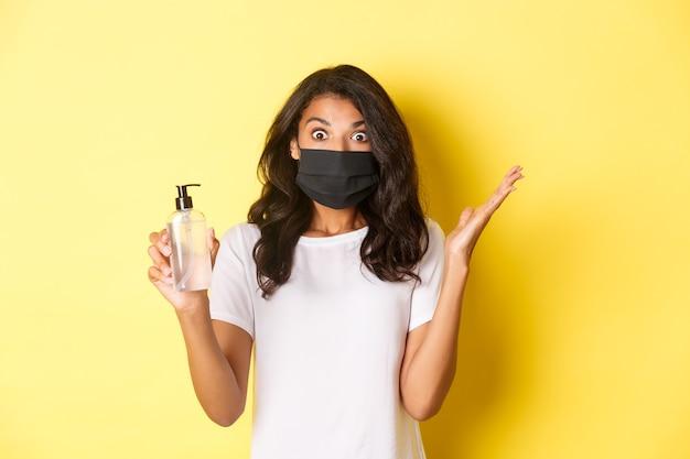 Konzept von covid-19, sozialer distanzierung und lebensstil. bild einer aufgeregten afroamerikanischen frau, die gesichtsmaske trägt, die hände überrascht hochhebt, händedesinfektionsmittel hält, gelber hintergrund.